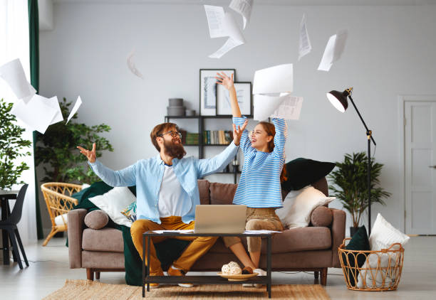 married couple with bills receipts documents and laptop at home - bills couple imagens e fotografias de stock