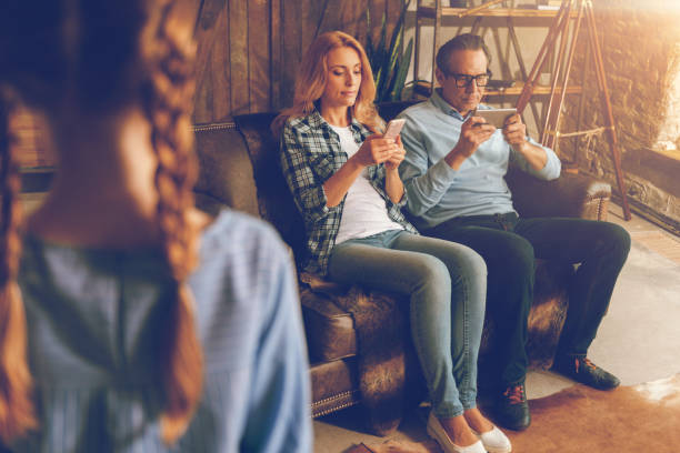 Married couple with phones ignoring their child Lack of love. Selective focus on totally absorbed in their smartphones husband and wife relaxing on a sofa and ignoring their little daughter seeking for a bit of attention. ignoring stock pictures, royalty-free photos & images