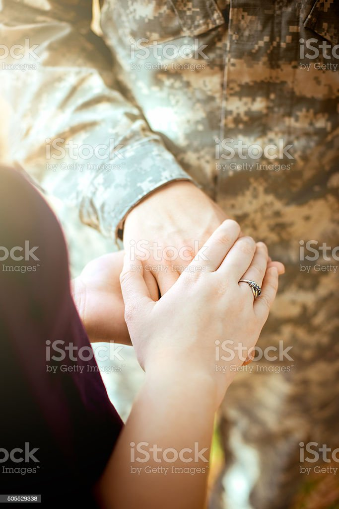 Married military couple holding hands stock photo