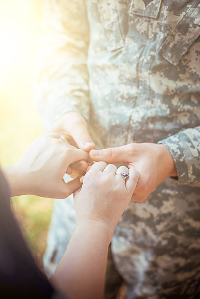 married military couple holding hands - wife stock photos and pictures