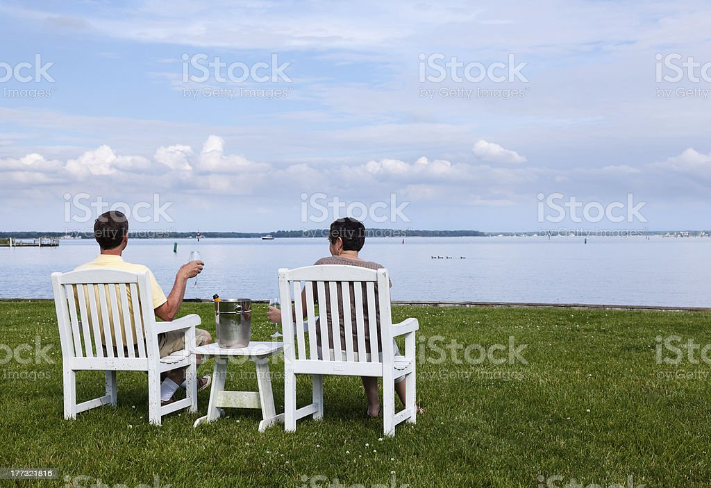 Married retired couple by bay with champagne stock photo