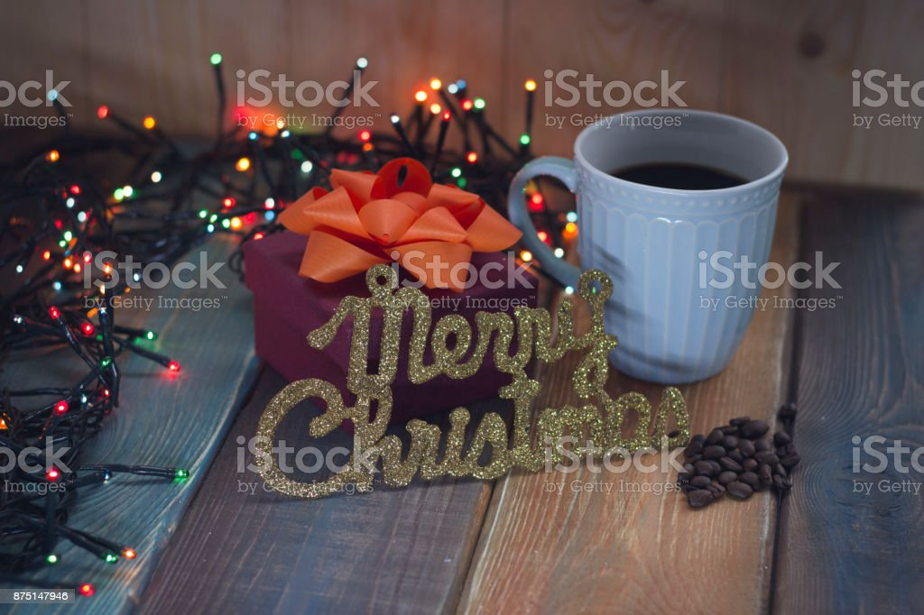 Marry Christmas and a blue cup of coffee and a box on the table stock photo