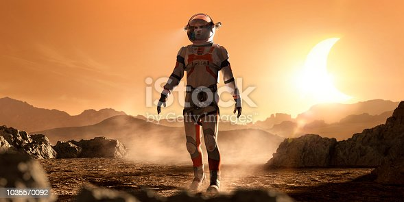 A male astronaut dressed in a spacesuit and helmet with heads up display walking through barren rocks and dusty landscape on mars. The spaceman is alone and is walking during a solar eclipse of the evening sun under an orange sky.