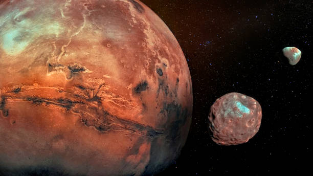 Mars with its two cratered moons Phobos and Deimos. Elements of this image furnished by NASA.