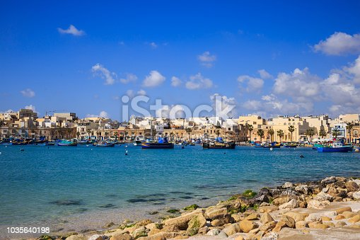 Marsaxlokk historic port with many boats in transparent sea and beach with stones, Malta. Blue sky with few white clouds and village background. Destination for vacation, relaxing and fishing.