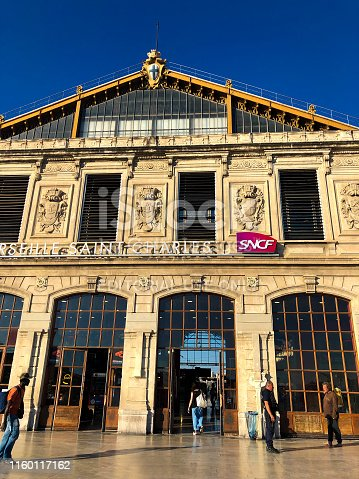 Marseille, France: A police officer chats with a barefoot man as a traveler enters the sunlit Marseille Saint Charles train station at dusk (golden hour). The station dates from 1926.