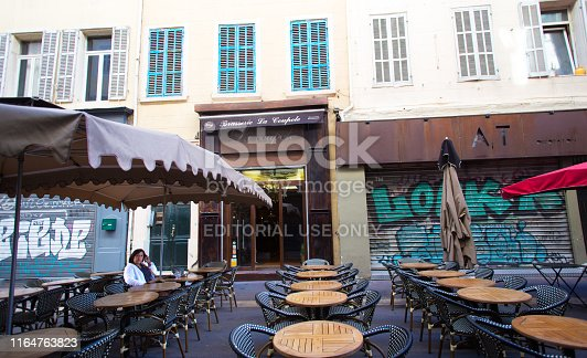 Marseille, France: A mature woman relaxes outside at a sidewalk cafe in early morning in downtown Marseille.