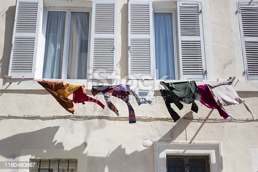Marseille Architecture: Laundry line with blowing clothes against a white sunlit building. Shot in the Panier district of Marseille.