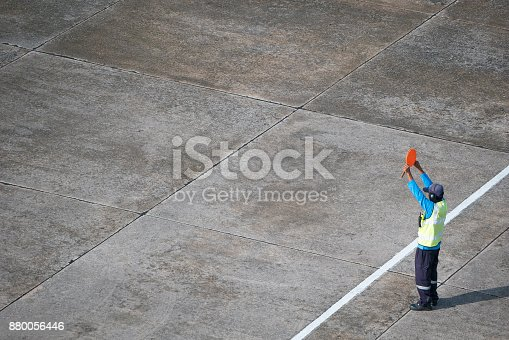 istock Marshaller signalling to stop the aircraft 880056446