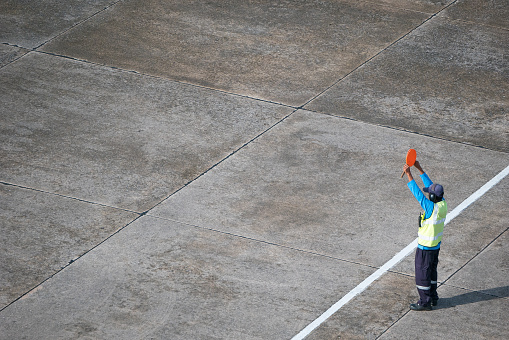 Marshaller signalling to stop the aircraft at the airport apron