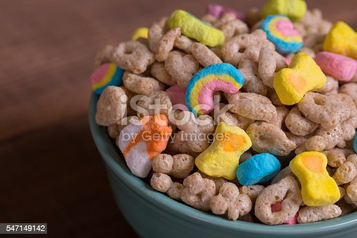 Colorful marshmallow cereal in a blue bowl on a weathered wood background