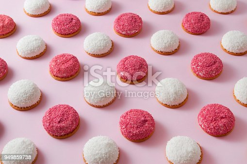 Pattern with sweet strawberry and coconut flavored marshmallow cookies on pink background. Minimal food background concept from above view