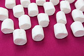 istock marshmallows on a pink background. Fonso sweets with place for text. Lot of whole white sweet fluffy marshmallow copyspace flatlay on  fuchsia, purple background 1249535610