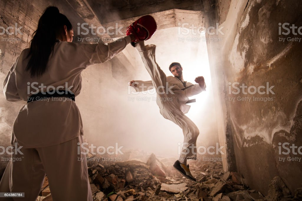 Martial artist practicing jump kick with female partner among ruins. stock photo