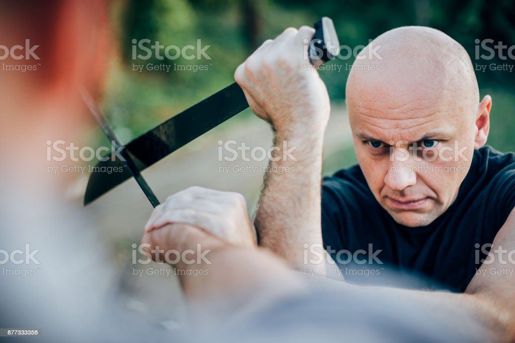 Martial arts instructor demonstrates machete fighting. Long knife weapon training stock photo