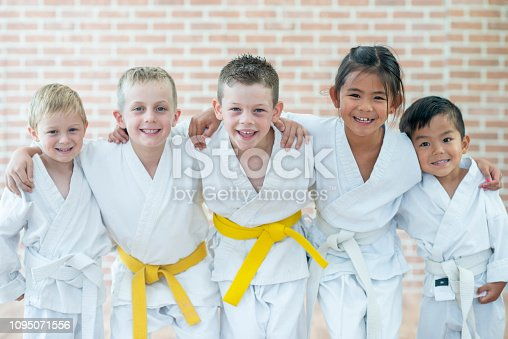Five kids are posing together and embracing while attending their martial arts class.