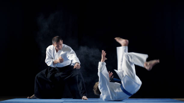 Martial Arts Master Wearing Hakamas Teaches Young Student Aikido Technique of Throwing over the Shoulder Shot Isolated on Black Background. stock photo