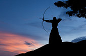 Abstract photo of man silhouette demonstrating martial arts with bow in front of sunset sky