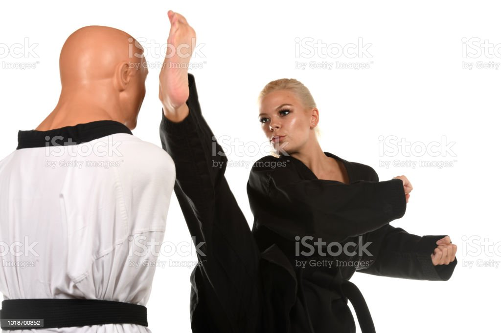 Martial artist kicking a training mannequin in the head.