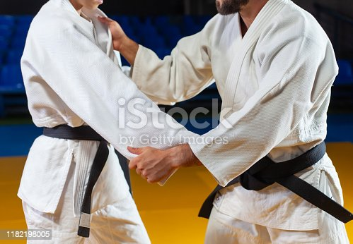 istock Martial arts. Sparing Portners. Sport man and woman in white kimono train judo captures in the sports hall. Crop photo 1182198005