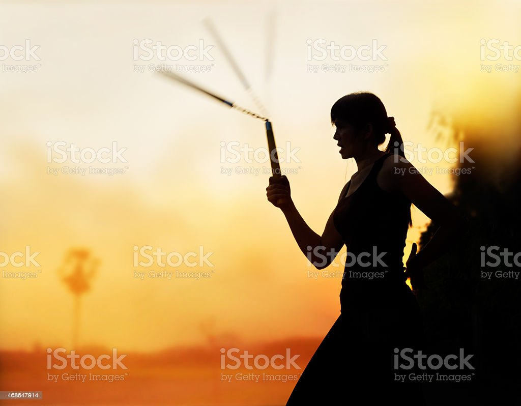 martial arts, women and nunchaku in hands silhouette in sunset stock photo