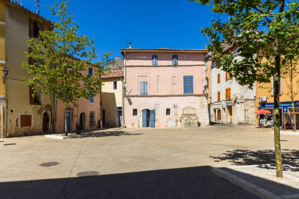 Martigues - France Martigues, France - June 25, 2017:Two people shelter from the sun in a shady corner in a small square in the old center of Martigues. southern charm stock pictures, royalty-free photos & images