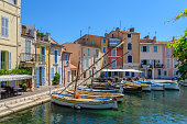 Martigues, France - June 25, 2017: View of the small harbor in the old center of Martigues, a tourist destination with small bars and adjacent restaurants.
