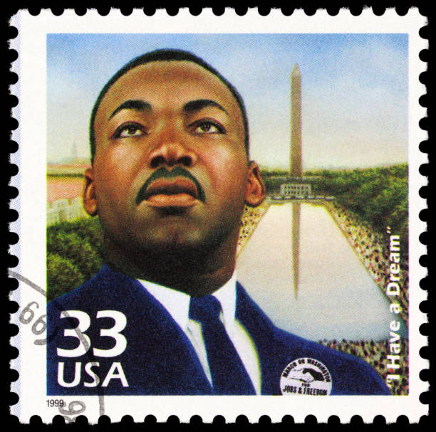 "Martin Luther King Jr ""Seattle, USA - June 23, 2012: A 1999 USA postage stamp with an image of Martin Luther King, Jr. King is depicted wearing a badge that reads: MARCH ON WASHINGTON FOR JOBS & FREEDOM, and in the background is the Washington Memorial and a large crowd of people. The stamp commemorates the August 28, 1963 demonstration in Washington, D.C."" mlk stock pictures, royalty-free photos & images"