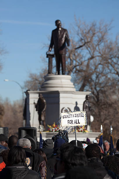 """Martin Luther King Parade March equality sign Denver Denver, Colorado, U.S.A. - January 21, 2013: A sign with """" EQUALITY AND JUSTICE FOR ALL"""" stands above crowds of people at the Martin Luther King Jr. statue in Denver's City Park for his annual parade and march. martin luther king jr photos stock pictures, royalty-free photos & images"""