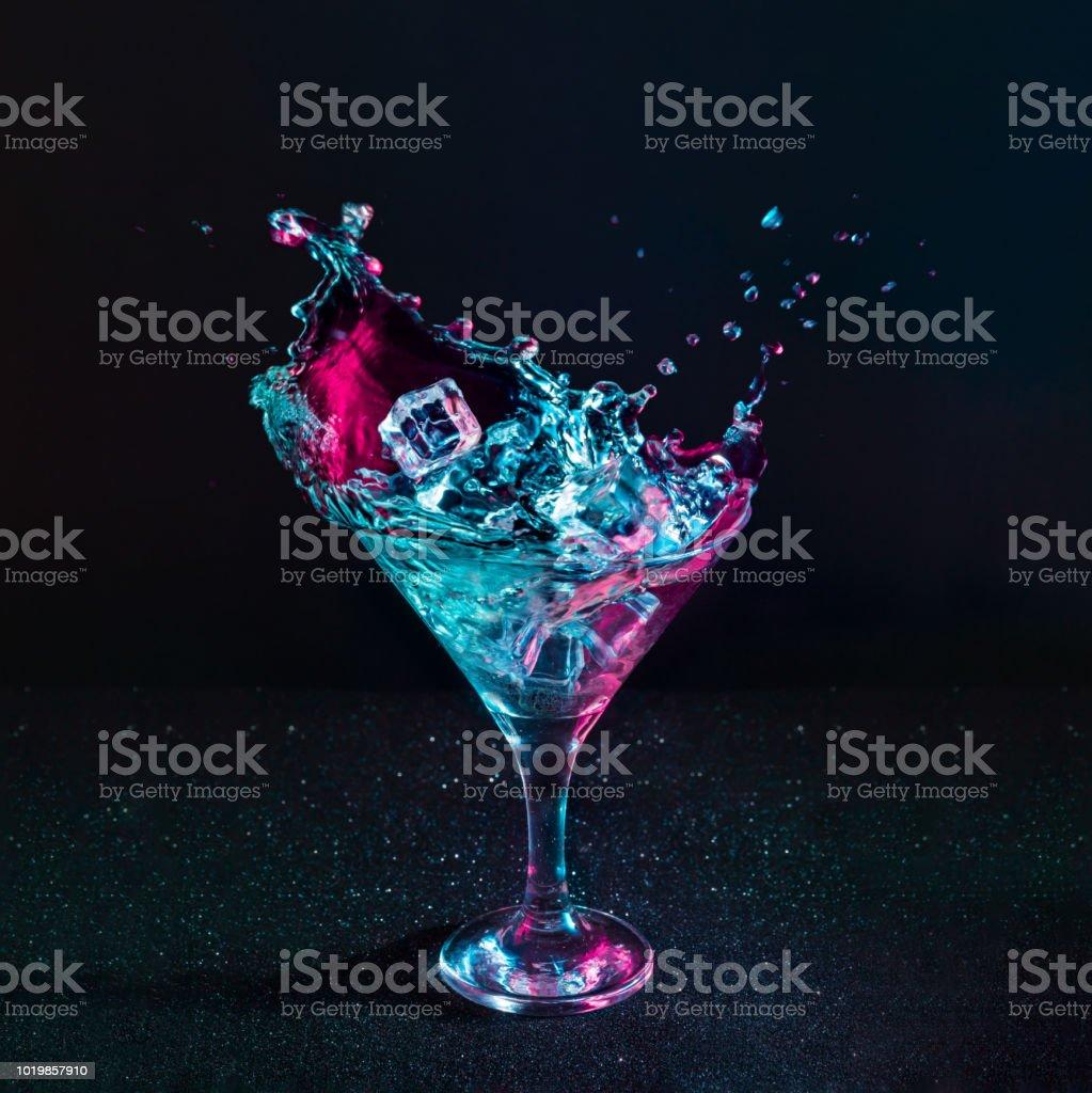 Martini kokteyl içki sıçrama neon yanardöner pembe ve mavi renklerde buz küpleri ile. - Royalty-free Aydınlık Stok görsel