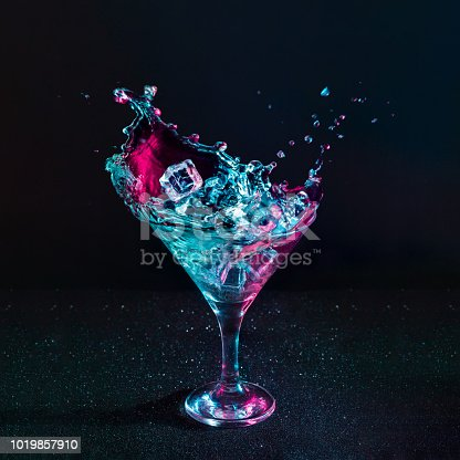 istock Martini cocktail drink splash with ice cubes in neon iridescent pink and blue colors. 1019857910