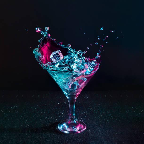 martini kokteyl içki sıçrama neon yanardöner pembe ve mavi renklerde buz küpleri ile. - kokteyl i̇çki stok fotoğraflar ve resimler