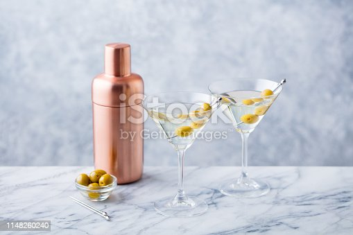 istock Martini cocktail with green olives, shaker on marble table background. 1148260240