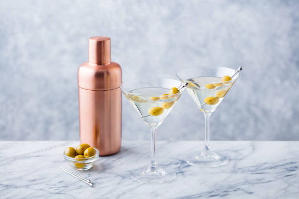 Martini cocktail with green olives, shaker on marble table background. Martini cocktail with green olives, shaker on marble table background cocktail shaker stock pictures, royalty-free photos & images