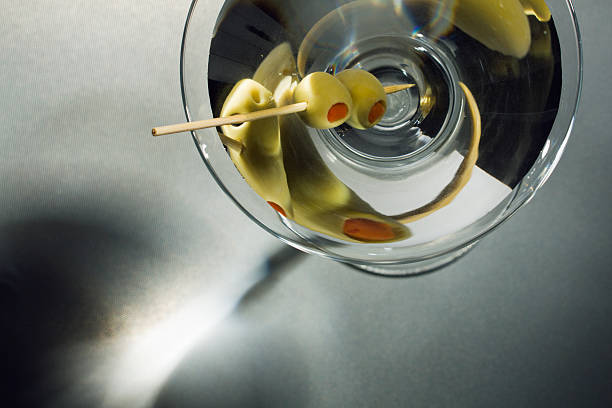 Martini Glass Cocktail Drink withToothpick Skewered  Olives Overhead View A chilled Martini garnished with two pimento stuffed green olives skewered by a toothpick, seen from a stylish overhead view. The hard liquor alcoholic beverage is a bar mixed drink and glamorous celebration party refreshment. Horizontal close-up view with copy space, on gray shadowy background with no people.  martini stock pictures, royalty-free photos & images