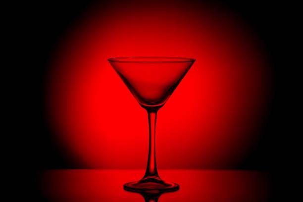 martiniglas in een sombere bloedrode licht. - verleiding stockfoto's en -beelden