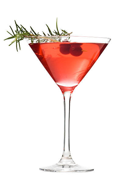Martini Glass of Cosmopolitan Cocktail, Red Alcoholic Beverage on White A red cranberry cosmopolitan with a sprig of rosemary in a martini glass. The festive alcoholic beverage is isolated on a white background. martini glass stock pictures, royalty-free photos & images