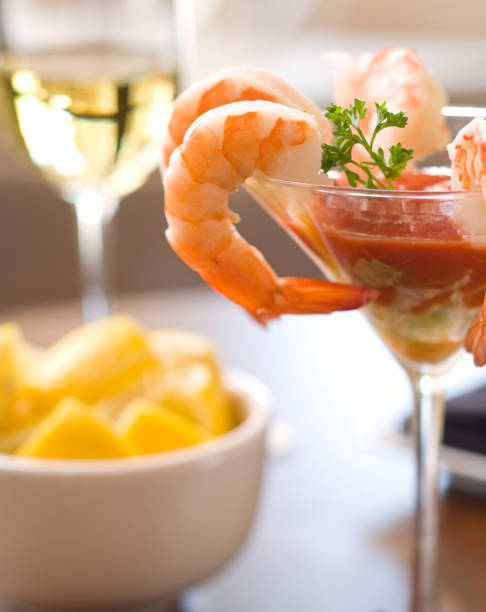 A martini glass of shrimp cocktail and a bowl of lemons stock photo