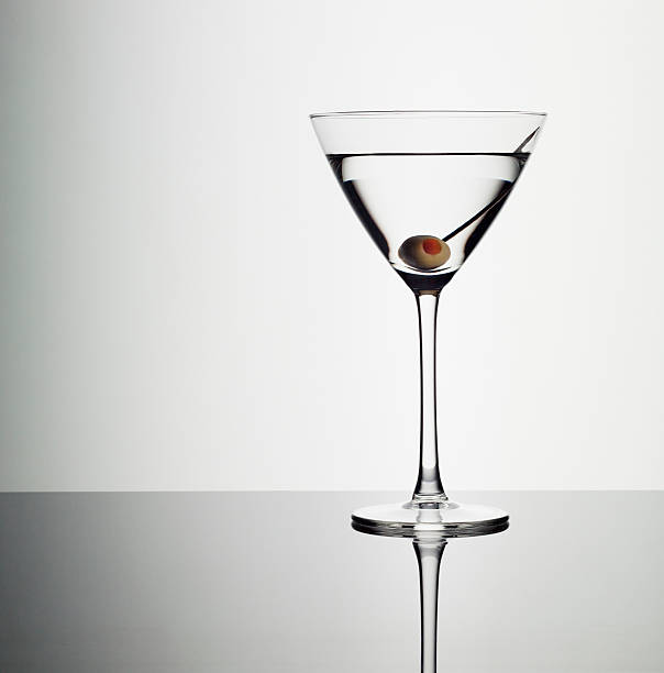 Martini in glass with green olive  martini stock pictures, royalty-free photos & images