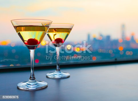 Couple of martini glasses with city view.