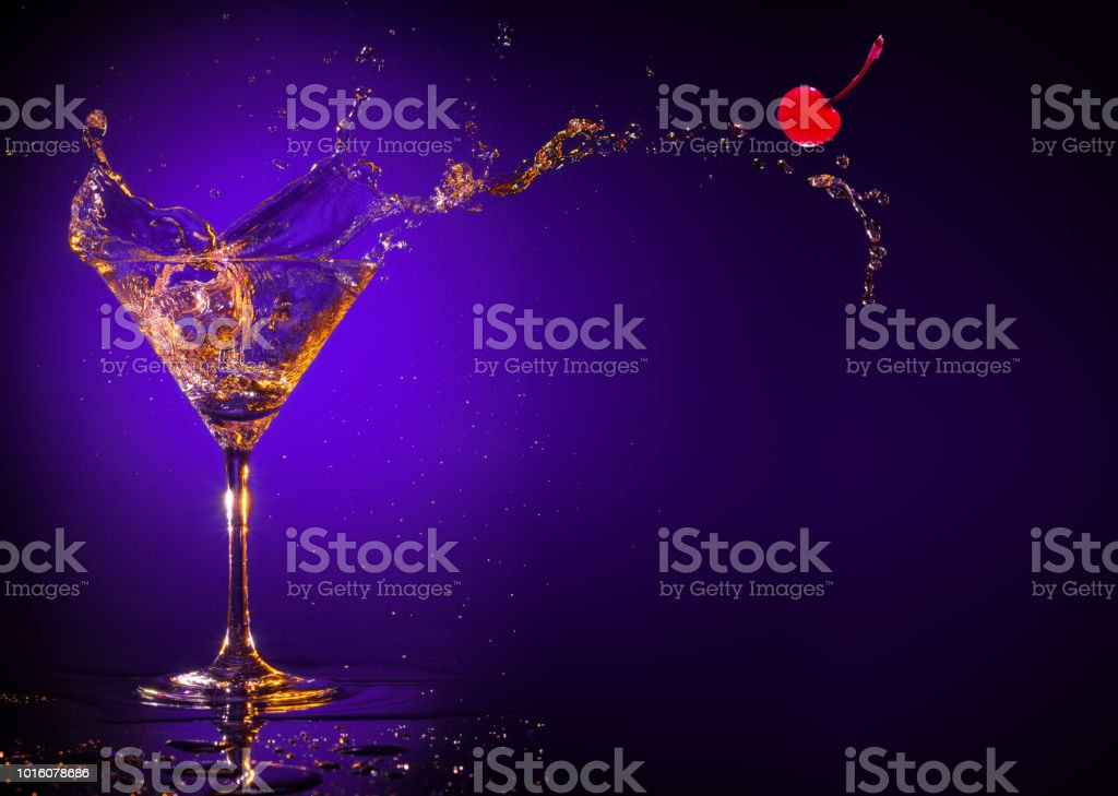 red cherry splashing out of a martini glass on a purple background