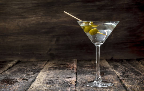 Martini with olives. Martini with olives. On a wooden background. martini stock pictures, royalty-free photos & images