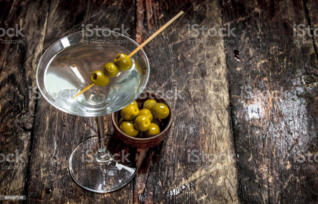 Martini with olives. Martini with olives. On a wooden background. Alcohol - Drink Stock Photo