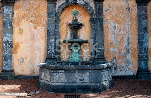Fountain that survived the Mount Pelée eruption in front of the ruins of the historic Theater in the town of Saint-Pierre, Martinique.