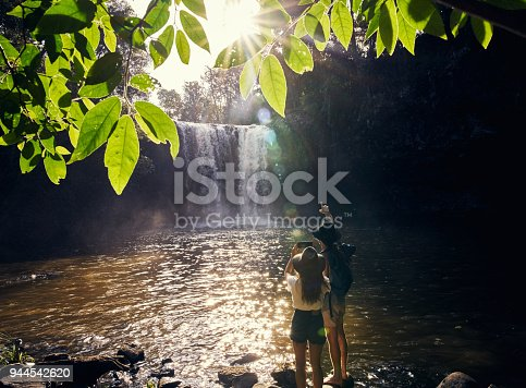 Shot of a young couple taking photos of a waterfall over a lake