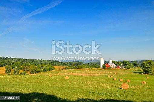 The hay has been mowed and baled, the sky is blue and the dairy farm is ready for winter.