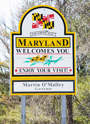 """Emmitsburg, Maryland, USA - March 7, 2011: """"Maryland Welcomes You"""" billboard sign on Route 15 southbound just north of Emmitsburg, MD at the Maryland-Pennsylvania state border line."""