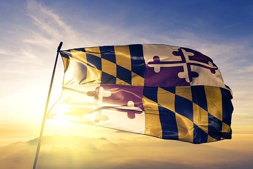 Maryland state of United States flag on flagpole textile cloth fabric waving on the top sunrise mist fog