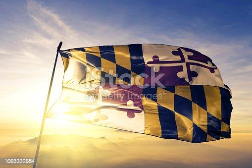 istock Maryland state of United States flag textile cloth fabric waving on the top sunrise mist fog 1063332654