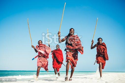 Masai warriors running on beautiful african beach, demonstrating their traditional hunting methods (zanzibar, Tanzania),